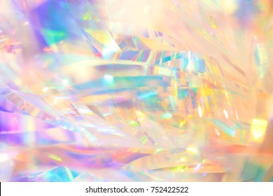 Rich vibrant polished elegant abstract background texture of holographic holiday foil ribbon decoration in pastel gold, aqua and purple colors with shiny crystal sparkling bright light reflections