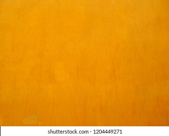 a rich warm golden yellow painted wall background with brush marks and weathered antique effect