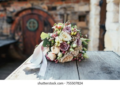 Rich wedding bouquet of white and violet roses lies on wooden table