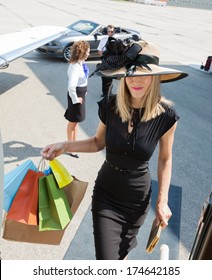 Rich woman carrying shopping bags while boarding private jet with pilot and airhostess in background at airport terminal