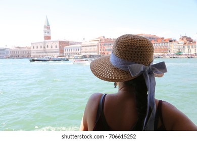 Rich young woman with straw hat in tourist sight in the city of Venice in Italy