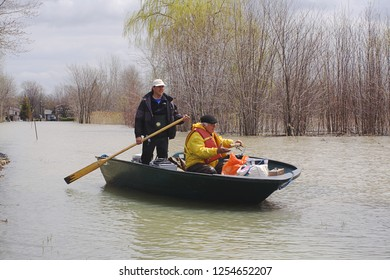 Richelieu River, Quebec/Canada - May 7, 2011   Homeowner with belongings being rescued in boat from flood waters from record water elevation southwest of Montreal
