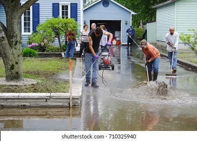 Richelieu Valley, Quebec, Canada June 11, 2011:  Volunteers cleanup outside of a suburban home follow catastrophic flooding