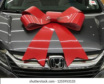 Richfield, MN/USA. December 10th, 2018.  A seasonal red holiday bow is placed on the hood of a new Honda Odyssey on display in Minnesota.