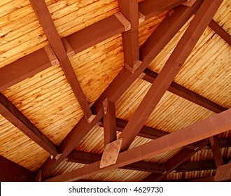 A richly colored wooden slat ceiling with exposed beams