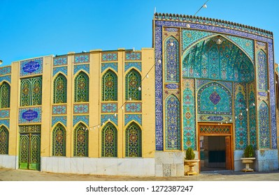 The richly decorated entrance portal of Imam Zadeh Jafar Shrine with intricate tilework in blue gamma, Yazd, Iran.
