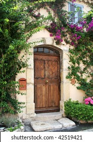Richly-grained wooden door to private stucco villa in medieval village of Mougins, France.  Flowering vines frame the doorway, and there's a classic blue-shuttered window above.