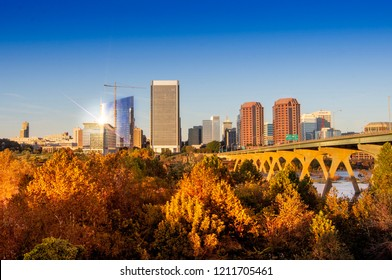 Richmond, VA—October 22, 2018; sunset light reflects off of bridge crossing the James river, shoreline park trees and buildings in downtown Richmond