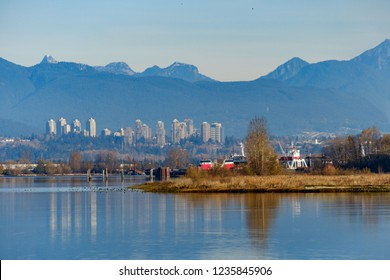 Richmond, BC/Canada - 11182018: river bank with water reflecting the city and forest behind under blue sky