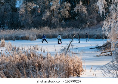 RICHMOND HILL, ONTARIO - DECEMBER 23: Group of teenagers playing hockey on a frozen pond on December 23, 2013 in Richmond Hill, Ontario, Canada.
