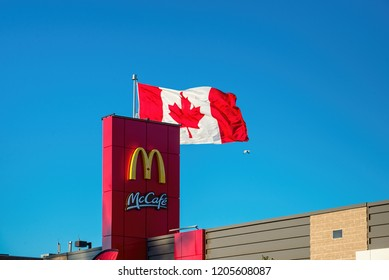 Richmond Hill, Ontario - October 14, 2018: McCafe sign and Canadian flag on a new McDonalds restaurant building