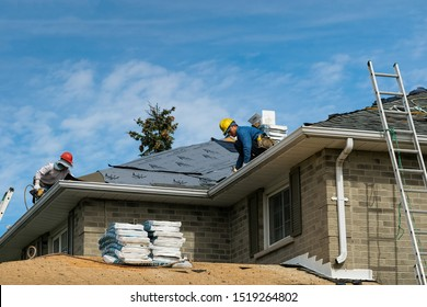 Richmond Hill, Ontario - September 29, 2019: Two workers installing a new shingles roof on a brick house