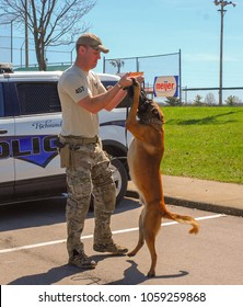 Richmond, KY US - March 31, 2018 - Easter Eggstravaganza A K9 Officer demonstrates canine techniques and training exercises with his K9 for a crowd, Mallinois bite dog, standing