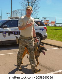 Richmond, KY US - March 31, 2018 - Easter Eggstravaganza A K9 Officer demonstrates canine techniques and training exercises with his K9 for a crowd, Mallinois bite dog, walking beside the officer