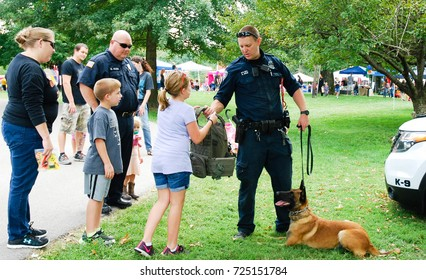Richmond, Ky US - September 9th, 2017 - Kid's Fest  An K9 officer hands a tactical bullet proof vest to a little girl during a demonstration while his dog lies beside him