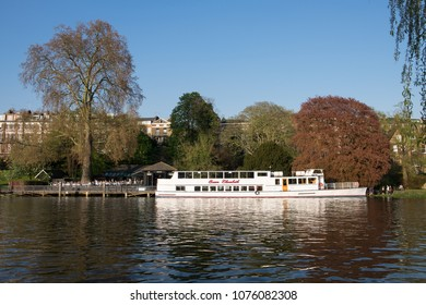 RICHMOND, SURREY, UK - APRIL 20, 2018: river cruise boat moored on the bank of the Thames at Richmond, with crowd of people nearby enjoying fine spring weather.