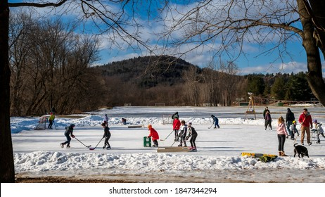 Richmond, Vermont, USA. February 11, 2019: Children playing hockey and ice skating at the Richmond town park ice skating rink, February 11, 2019, Richmond, Vermont.