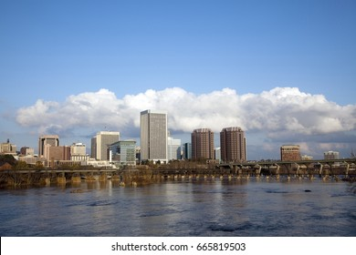 Richmond, Virginia cityscape skyline with blue sky and clouds on the James River.