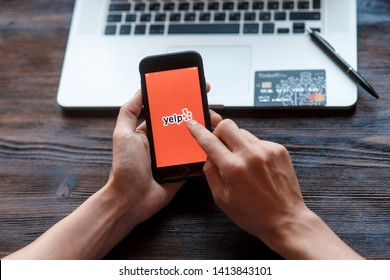 Richmond, Virginia, USA -30 May 2019: Woman holds Apple iPhone X with Yelp.com site on the screen. Search page. close up