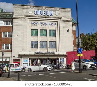 RICHMOND-UPON-THAMES, UK - SEPTEMBER 20, 2015:  Traffic and pedestrians pass the busy junction in front of the historic Richmond Odeon cinema with its amazing Art Deco designs.