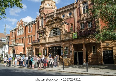 RICHMOND-UPON-THAMES, UK - SEPTEMBER 20, 2015: Visitors listen to a guide outside the historic theatre in Richmond-Upon-Thames.  Designed by Frank Matcham, the theatre was opened in 1899.