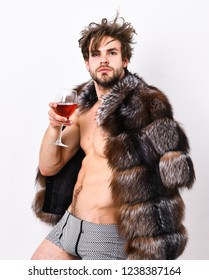 Richness and luxury concept. Guy attractive rich posing fur coat on naked body. Rich athlete enjoy his life. Sexy sleepy rich macho tousled hair drink wine isolated on white. Fashion and pathos.