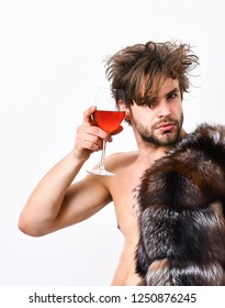 Richness and luxury concept. Rich athlete enjoy his life. Guy attractive rich posing fur coat on naked body. Sexy sleepy rich macho tousled hair drink wine isolated on white. Health and wellbeing.