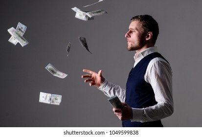 Richness and wealth concept. Successful entrepreneur on arrogant face wasting money. Man in formal wear, businessman throwing money on grey background. Banknotes, cash dollars fly in air around guy.
