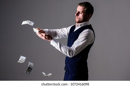 Richness and wealth concept. Successful entrepreneur on arrogant face wasting money. Banknotes, cash dollars fly in air around guy. Man in formal wear, businessman throwing money on grey background.