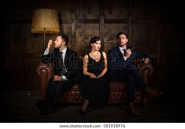 Richness, wealth concepts. Rivalry or competition between two men for elegant lady with red lips. Beautiful people sitting on sofa in restaurant.