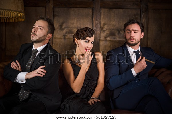 Richness, wealth concepts. Rivalry or competition between two handsome rich executive men for elegant lady with red lips. Beautiful people sitting on sofa in restaurant.
