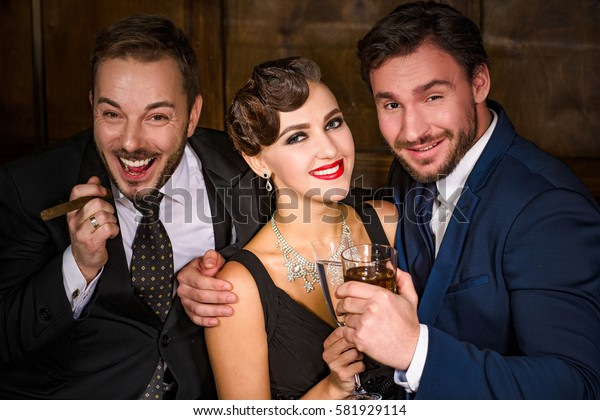 Richness, wealth, luxury concepts. Best happy friends having party in luxurious restaurant. People resting and relaxing with alcohol and cigars.