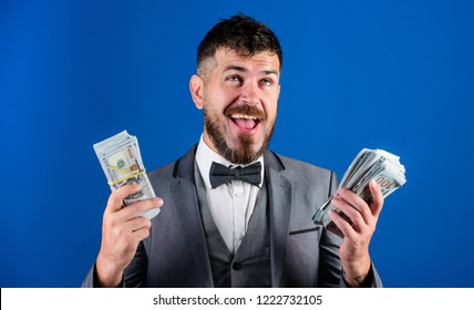 Richness and wellbeing concept. Get cash easy and quickly. Cash transaction business. Easy cash loans. Man formal suit hold pile of dollar banknotes blue background. Businessman got cash money.