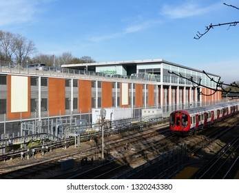 Rickmansworth, Hertfordshire, England, UK - February 22nd 2019: London Underground train passing Waitrose supermarket store in Rickmansworth