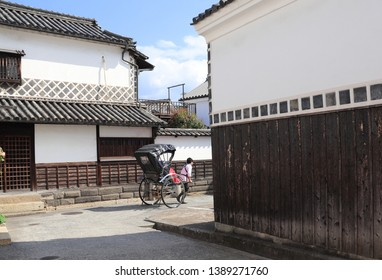 Rickshaw on medieval street with traditional japanese houses and storehouses in Bikan district, Kurashiki city, Japan