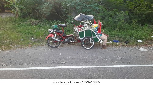 A rickshaw or pedicab motorcycle is parked on the side of the road and a rickshaw puller is waiting for passengers to arrive. village in Yogyakarta, Indonesia.Rickshaw using motor power