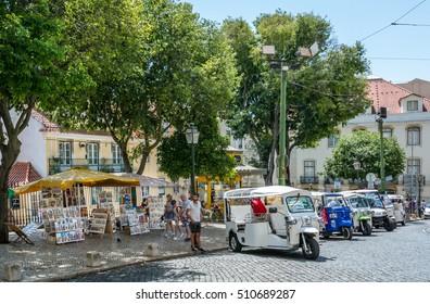 Rickshaws and kiosks near Se Cathedral in Lisbon, Portugal, June-28-2016
