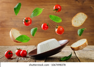 ricotta cheese with flying bread slices, tomatoes and Basil on a wood background. the toning. selective focus