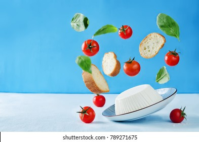 ricotta cheese with flying bread slices, tomatoes and Basil on a blue background with copy space. the toning. selective focus