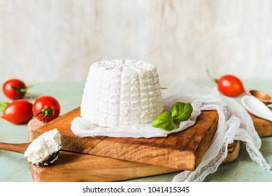 ricotta cheese on wooden base, teaspoon filled with ricotta cheese, basil,  tomatoes blurred in the background