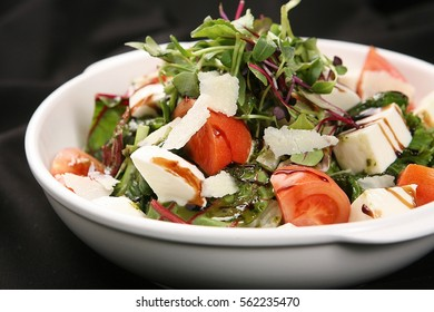 Ricotta Cheese with Tomatoes on top of a Fresh Salad