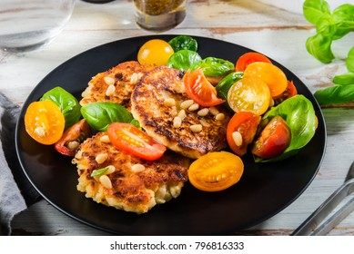 Ricotta pancakes with spinach, tomatoes, basil and pine nuts salad on the black plate, light background