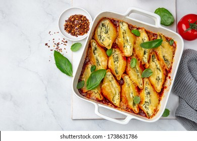 Ricotta and spinach stuffed shell  pasta with tomato sauce in white baking dish, white background, top view