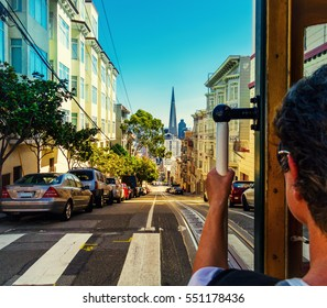 Ride with the cable car in San Francisco. Picture shows a person riding the famous MUNI train on Powell-Mason line down the hill to the bay with the famous landmark of Transamerica Pyramid in front.