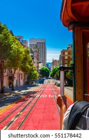 Ride with the cable car in San Francisco. The picture shows a person riding on the famous MUNI train on Powell-Mason line down the hill of Powell Street in San Francisco, California.