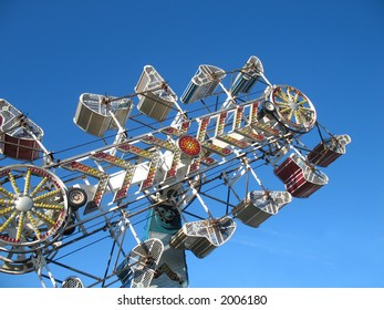A ride at the fairground with blue sky as backdrop.