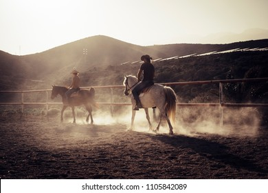ride horses lessons at the sunset with golden backlight. dust and two horses and caucasian cowboy style people. vacation and leisure outdoor in feeling with the nature and the animals