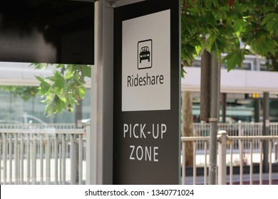 Ride share sign with a picture of a car in a box. Black and white sign. Green leaves on a tree widows and a metal fence in the background . Also has pick-up zone on the bottom