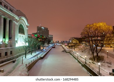 The Rideau canal under the snow with the Christmas lights in downtown Ottawa at night