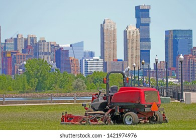 A Ride-On Lawnmower With A Number of Skyscrapers Visible in the Background
